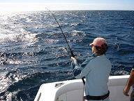 Image of woman fishing from the back of a boat in the open ocean