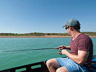 A recreational fisherman fishing from a boat